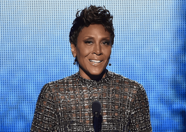 Robin Roberts speaking on stage in front of a microphone in a sequined gown.