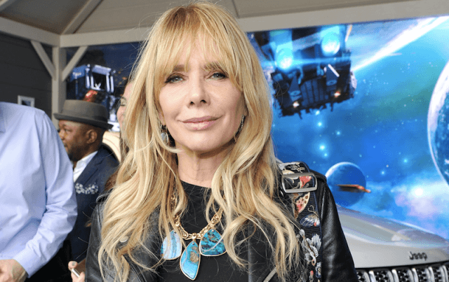 Rosanna Arquette smiles in a colorful jacket and necklaces.