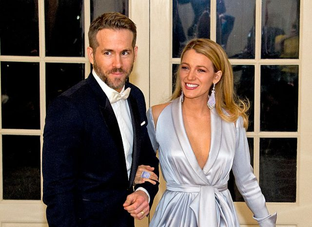 Blake Lively holds Ryan Reynolds arm while smiling.