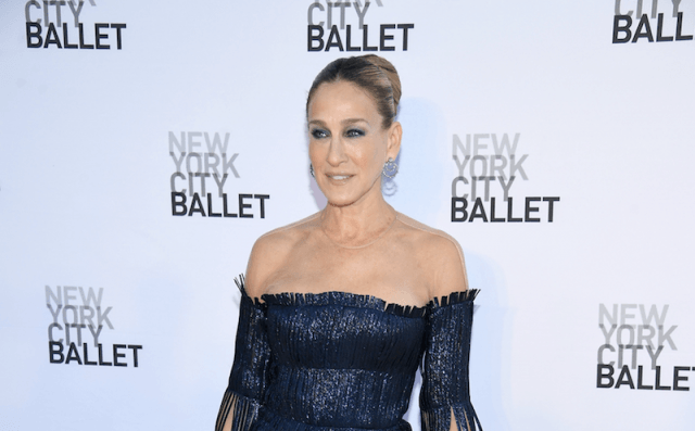 Sarah Jessica Parker standing in a blue fringe dress while holding a blue purse down at her side.
