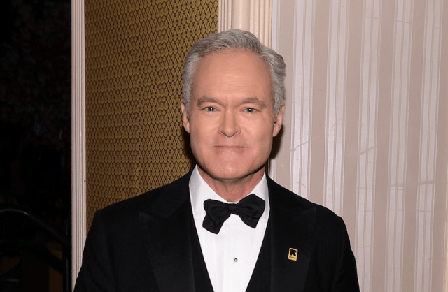 Scott Pelley smiles and stares straight ahead while wearing a black suit and bowtie.