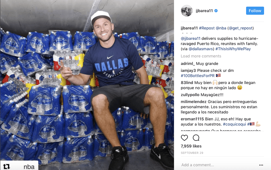 JJ Barea sitting in front of stacks of bottled water