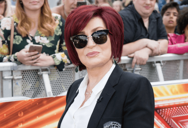 Sharon Osbourne wearing shades and a black blazer in front of a crowd of onlookers.