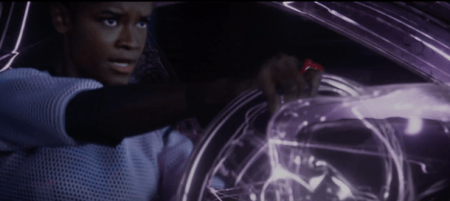 Shuri driving a car with a lit-up wheel.