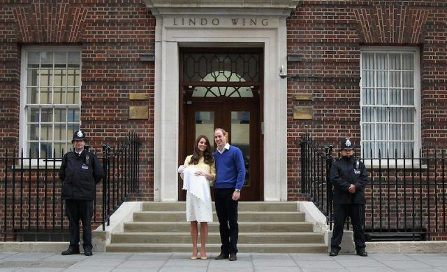 Kate Middleton holds her baby in her arms while Prince William stands next to her.
