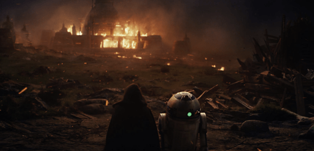 A building in the distance is on fire as two characters watch from afar among piles of rubble.