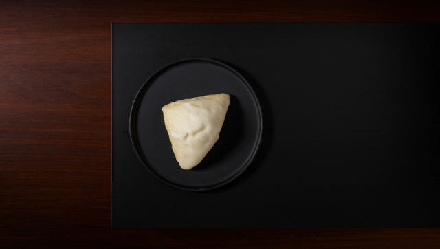 A petite Vanilla Bean Scone on a black plate.