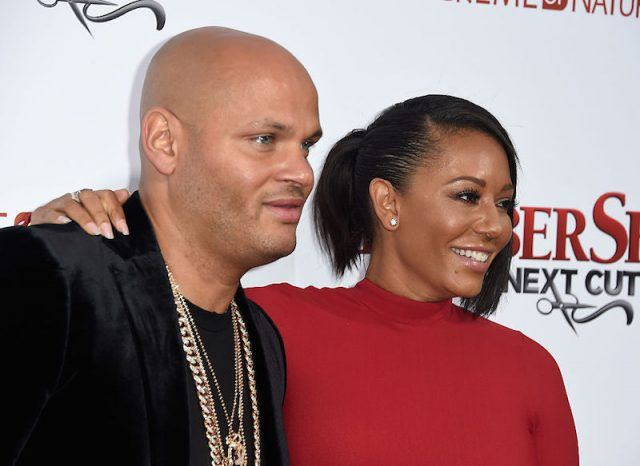 Stephen Belafonte and Melanie Brown pose for the paparazzi on a red carpet.