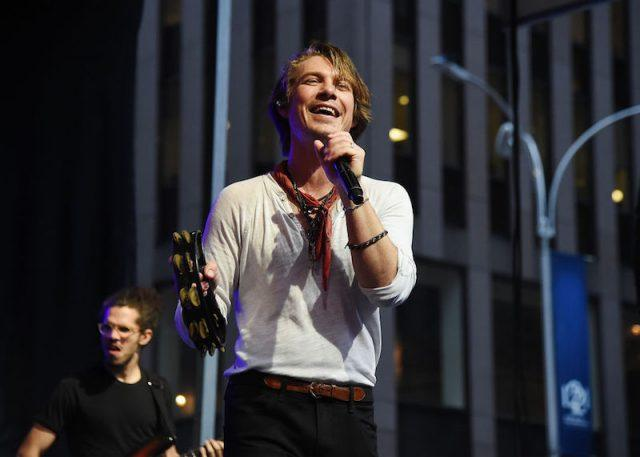Taylor Hanson performing on stage while holding a microphone.