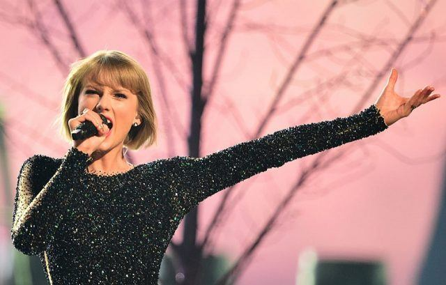 Singer Taylor Swift holds out her arm during a performance while holding a microphone and singing.