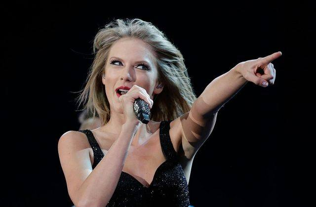 Taylor Swift performing on stage, holding a microphone with her right hand and pointing her left finger towards the audience.
