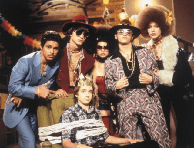 The cast of 'That 70's Show' in costumes in a basement.