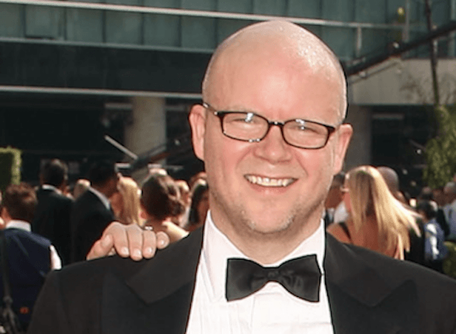 Toby Young smiling while wearing black glasses and a black tuxedo.