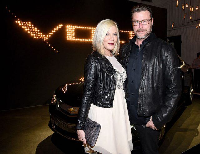Tori Spelling and Dean McDermott standing in front of a car.