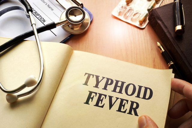 A doctor reading a book about Thypoid Fever.
