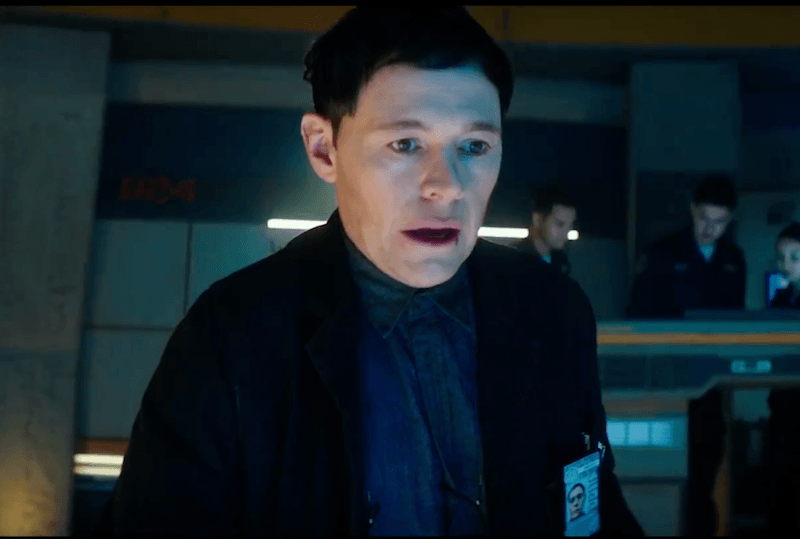Burn Gorman as Dr. Hermann Gottlieb makes a shocked face and looks ahead
