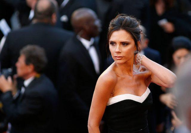 Victoria Beckham posing for the paparazzi in a black and white gown.