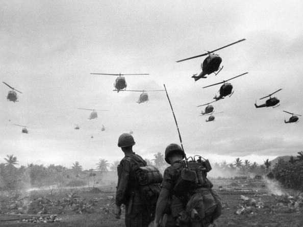 The second wave of combat helicopters of the 1st Air Cavalry Division fly over an RTO and his commander on an isolated landing zone