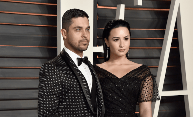 Demi stands next to Wilmer on a red carpet.