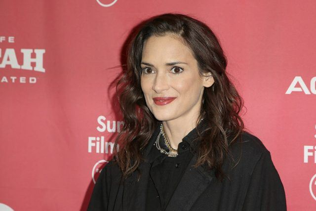 Actress Winona Ryder smiling in front of a pink backdrop at a red carpet event.