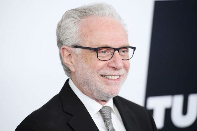 Wolf Blitzer smiles and poses for photographers while wearing a black suit and gray tie.