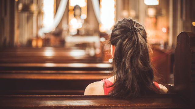 A woman sitting in a bench at a church.