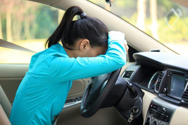 A woman lays her head on the steering wheel.