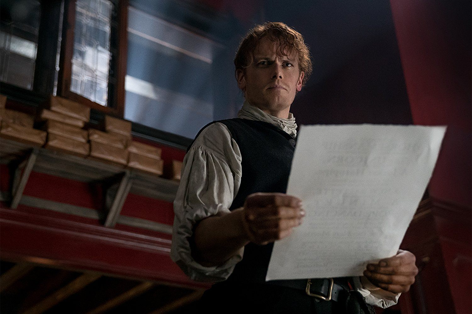 Jamie holding a piece of paper in Outlander