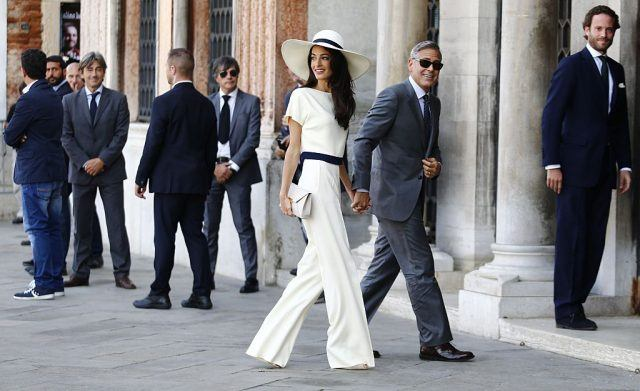 Amal and George Clooney walking while holding hands.