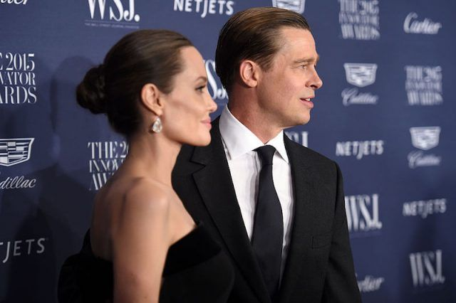 Angelina Jolie stands with Brad Pitt on a red carpet.