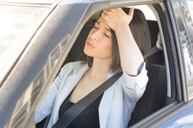 A woman holds her forehead in anger as she drives.