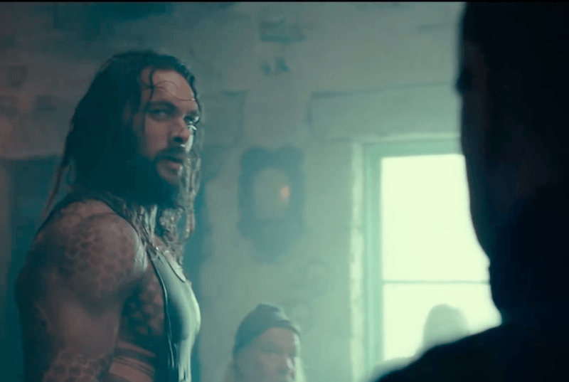 Aquaman looks to the side to a shadowed figure