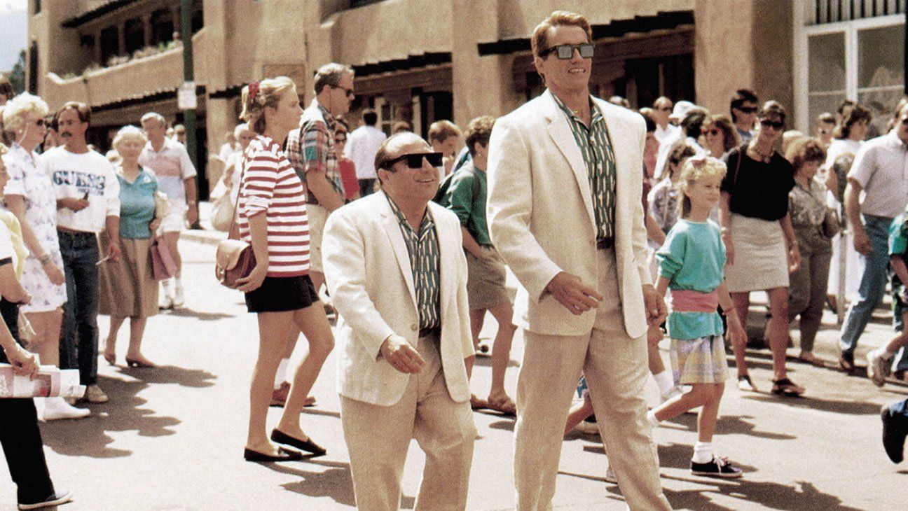 Arnold Schwarzenegger stands next to Danny Devito in white suits in Twins