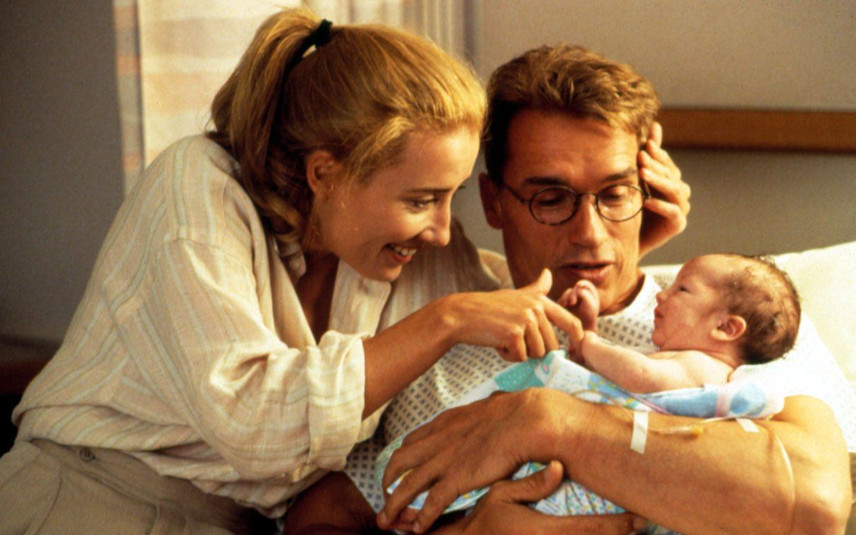 Arnold Schwarzenegger and Emma Thompson look at a baby in Junior