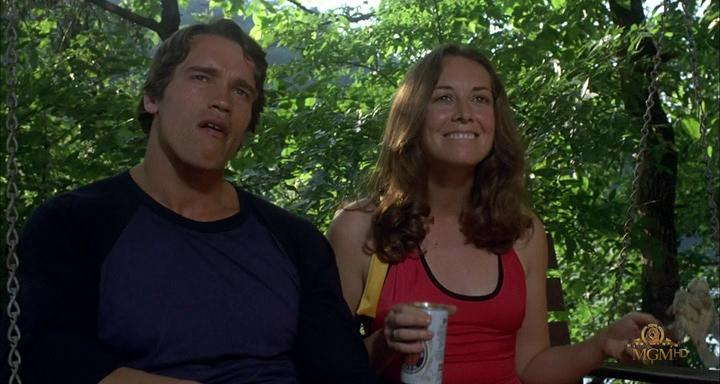 Arnold Schwarzenegger stands next to a woman holding a can in Stay Hungry