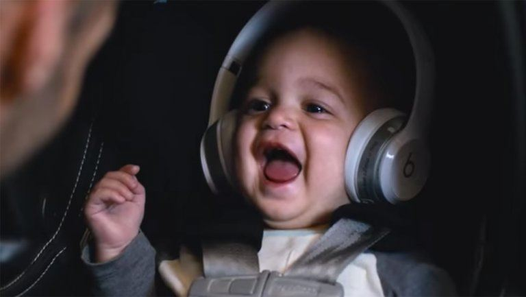 A baby with headphones on laughs in a car seat