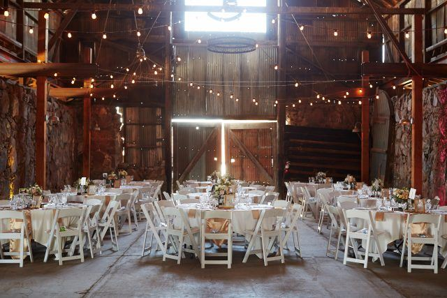 Barn wedding with lights and white tables.