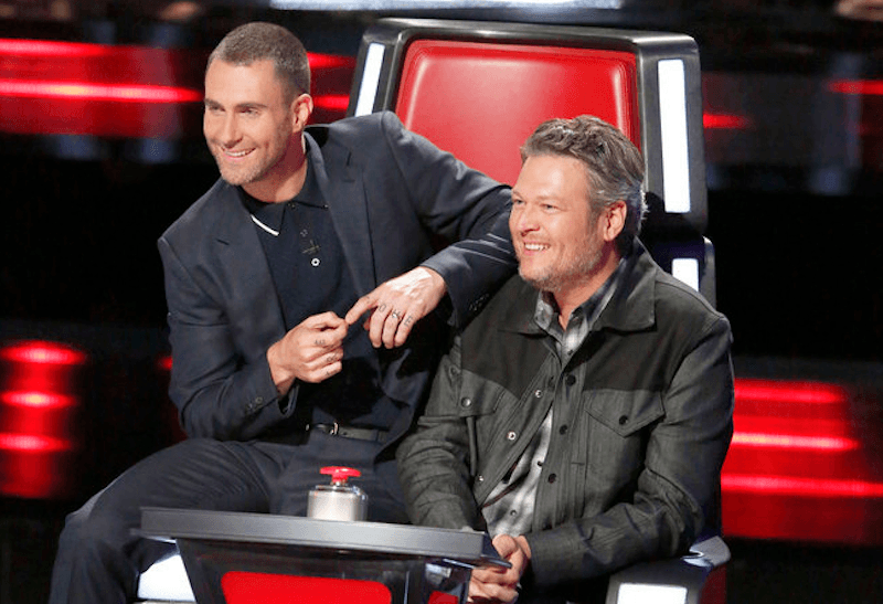 Adam Levine sits on Blake Shelton's chair on The Voice