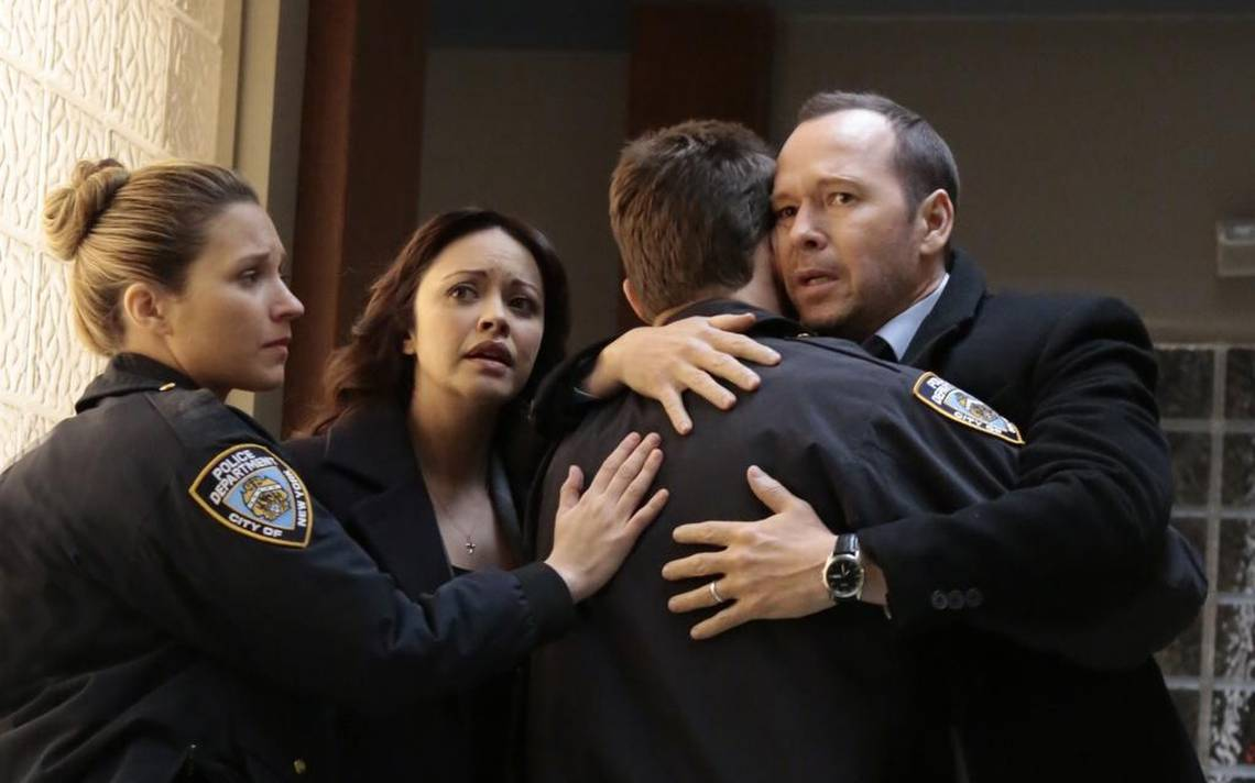 Two people hug two police officers
