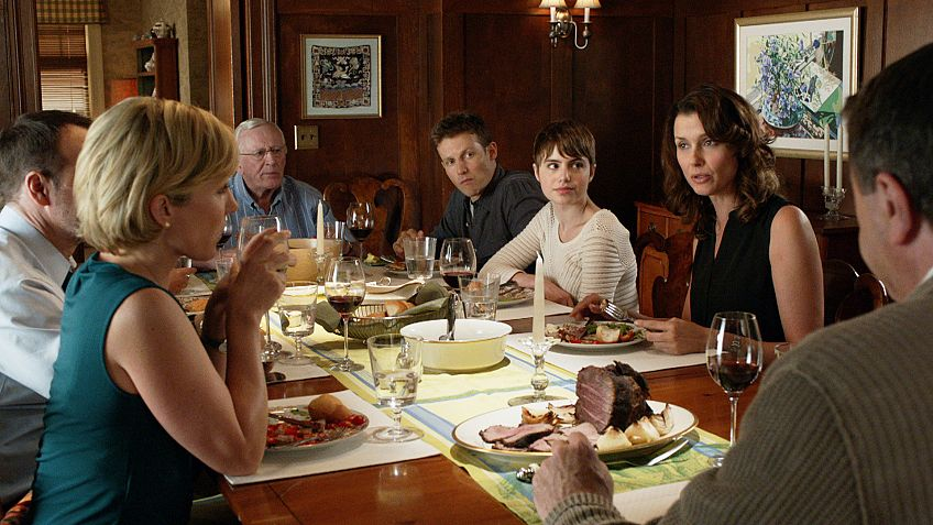 A group of people sit around a dinner table with food and wine in front of them