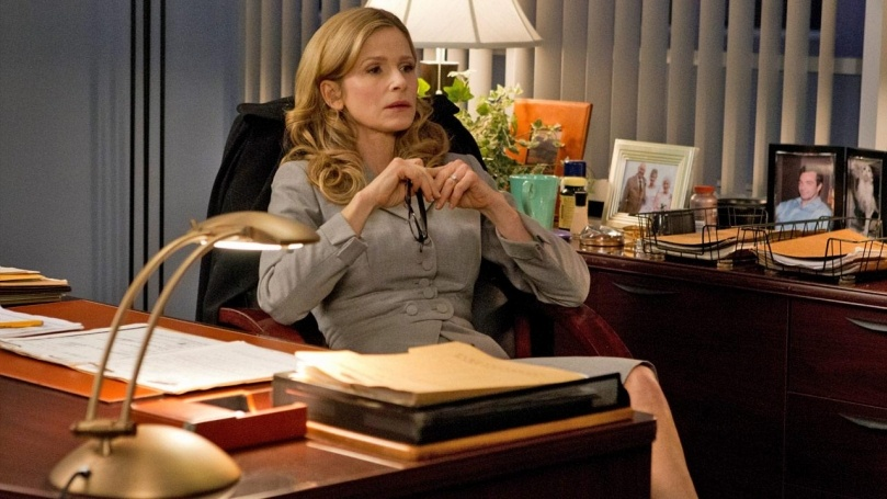 Kyra Sedgwick leans back in a chair at a desk
