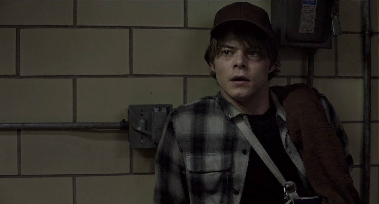 Charlie Heaton's Cannonball leans against a tile wall while wearing a flannel shirt