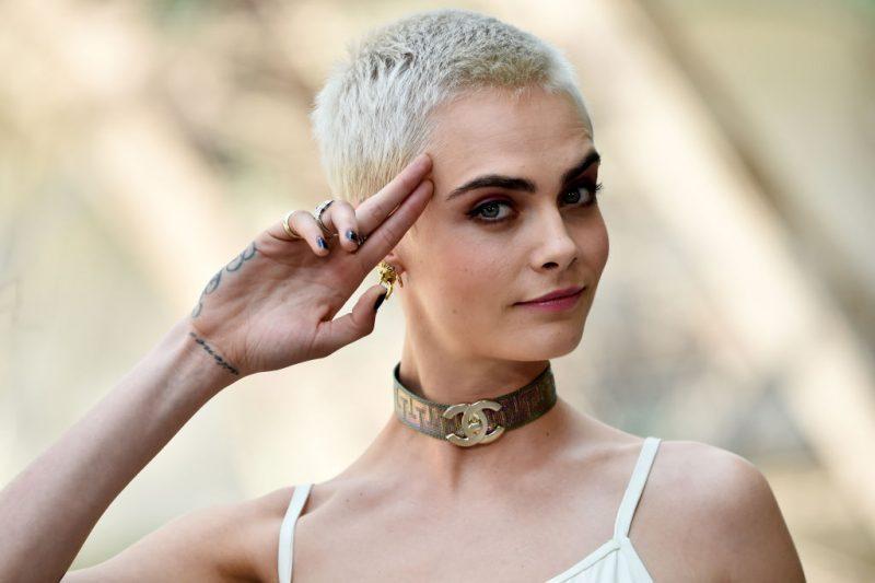 Cara Delevingne salutes a camera in July 2017