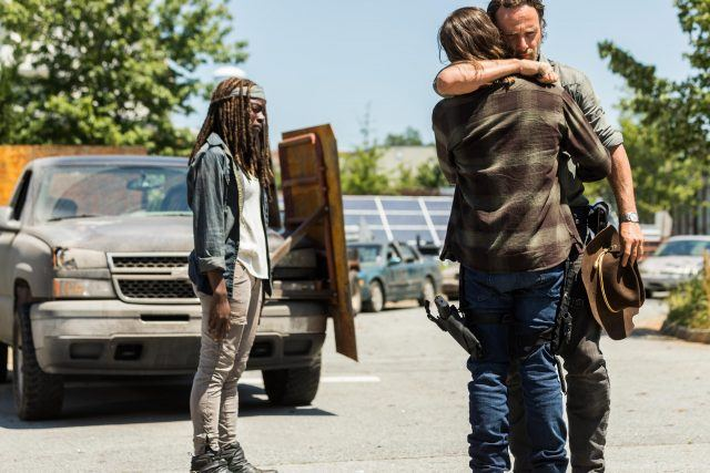 Carl and Rick embrace while Michonne stands away from them.