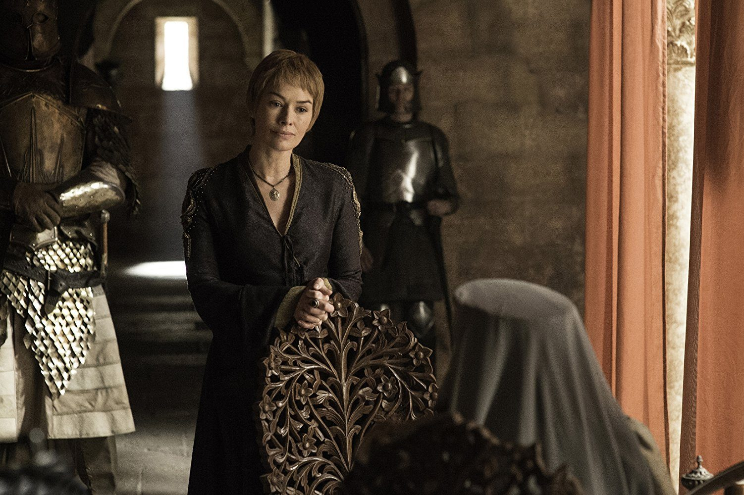 Cersei speaks to someone while standing next to armed guards.