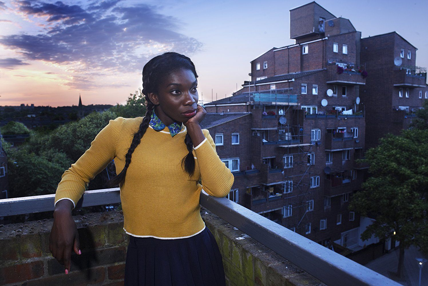 Michaela Coel stands on a balcony and leans her chin in her hand  in Chewing Gum