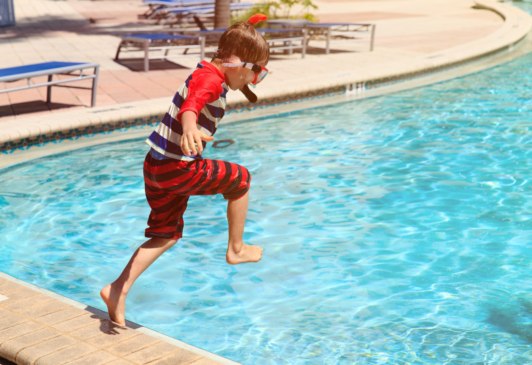 Boy jumping into the pool
