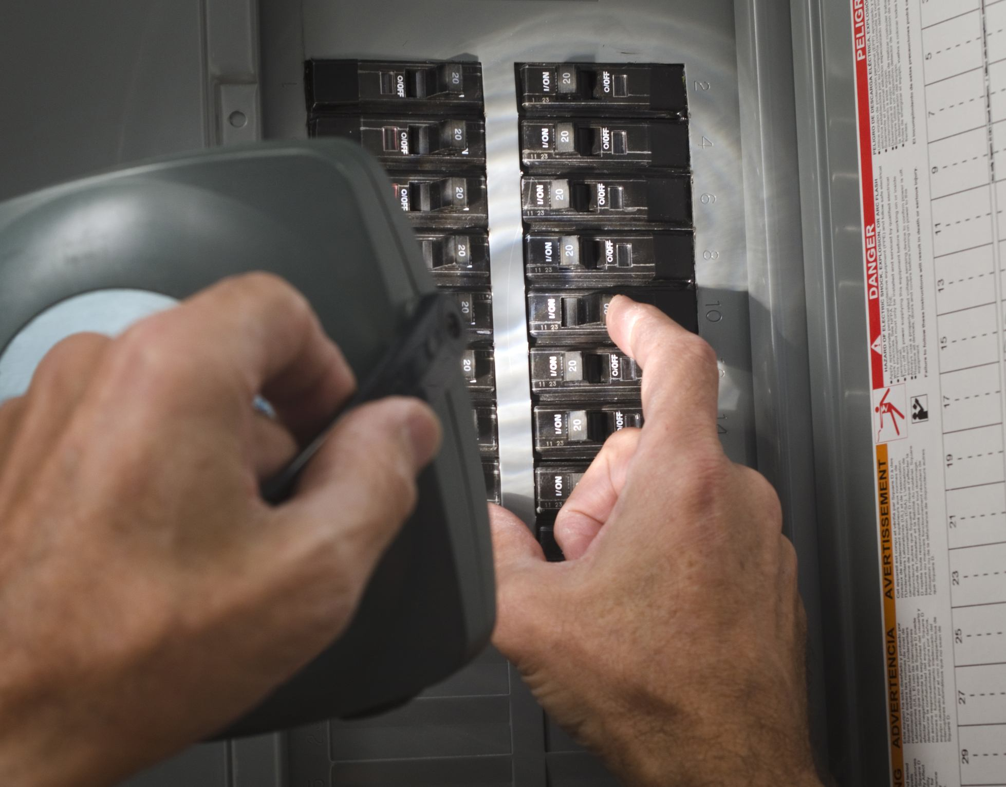 Man with flashlight looking at circuit breaker