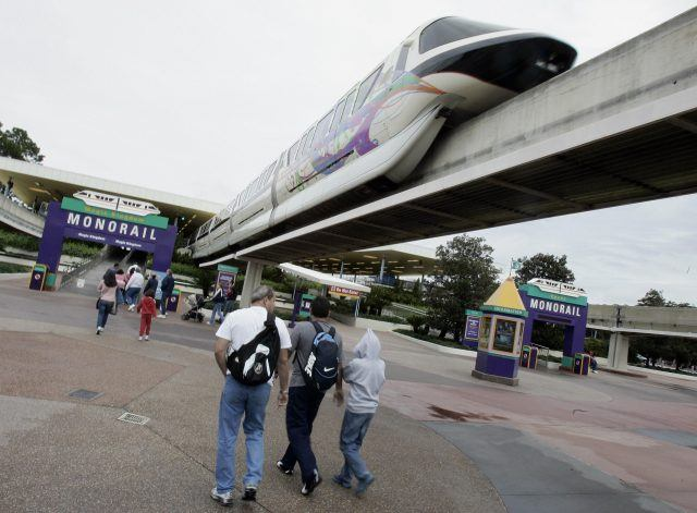 Disney World Monorail over a group of tourists.