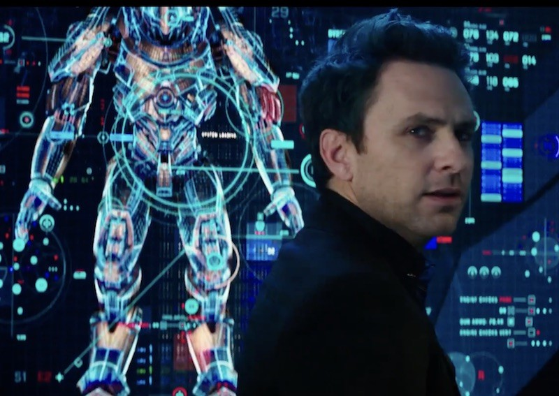 Charlie Day stands in front of a screen with an image of a robot